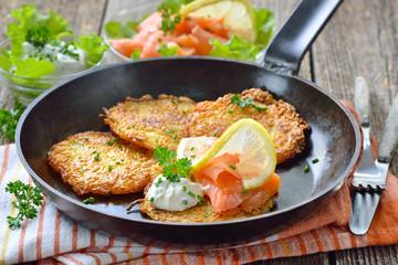 Resche Kartoffelpuffer mit Räucherlachs und Kräuter-Creme-Fraiche in der Eisenpfanne serviert – Crunchy potato pancakes with smoked salmon and sour cream with fresh green herbs