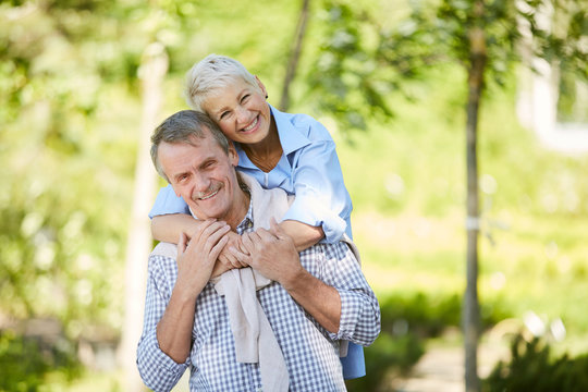 Portrait of carefree senior couple smiling at camera while enjoying date outdoors in Summer park, copy space