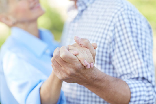 Close up of loving senior couple holding hands while dancing together outdoors, copy space