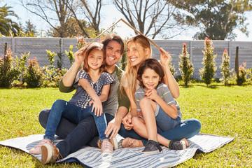 Familie mit Kindern hält Dach über Kopf