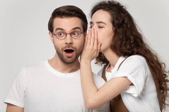 Girlfriend whispering in ear to boyfriend a secret studio shot