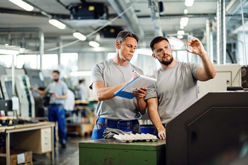 Industrial workers doing quality control of manufactured products in a factory.