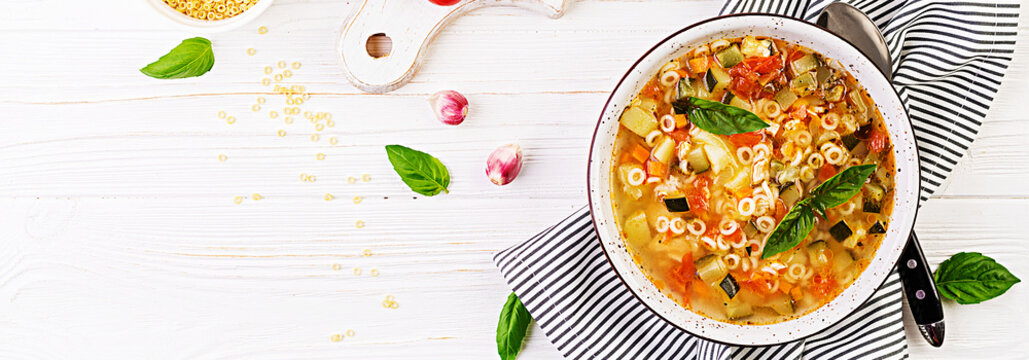 Minestrone, italian vegetable soup with pasta on white table. Vegan soup. Banner. Top view