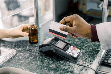 Cropped image of hands of African Man pharmacist holding credit card of client and hand of woman paying for Medicaments with credit card in pharmacy drugstore.