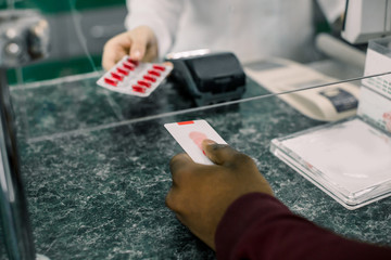 Cropped image of hands of woman pharmacist giving red pills to black man in drugstore. Man paying for Medicaments with credit card in pharmacy drugstore.