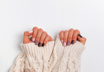 In de dag Manicure Woman;s hands in cozy knitted sweater shoing a manicure in pastel colors,