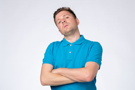 Man posing in studio with arms crossed and staring at camera with arrogant conceited look