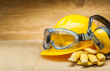 concept of safety. construction safety tools. yellow construction helmet leather gloves and earphones.