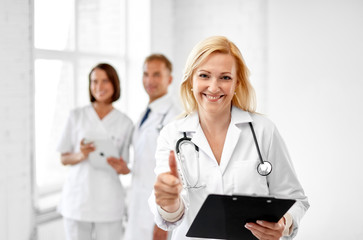 healthcare, medicine and profession concept - smiling female middle aged doctor with clipboard and stethoscope showing thumbs up at hospital