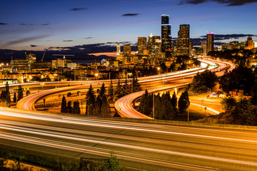 Foto op Canvas Seoel Seattle downtown skyline and skyscrapers beyond the I-5 I-90 freeway interchange after sunset with long exposure traffic trail lights from Dr. Jose Rizal or 12th Avenue South Bridge