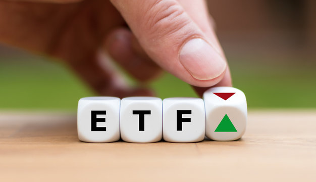 Hand is turning a dice and changes the direction of an arrow symbolizing that the value of an ETF (Exchange Traded Fund) is going up (or vice versa)