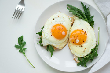 Sandwiches with ricotta cheese, arugula and fried egg on white wooden background. Selective focus. Healthy food concept