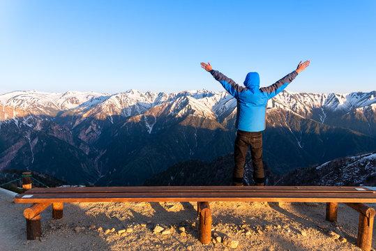 A man is seeing the scenery of Mount Tsubakuro Dake at sunset. Mountain range of Norther Japan Alps Chubu-Sangaku Park..