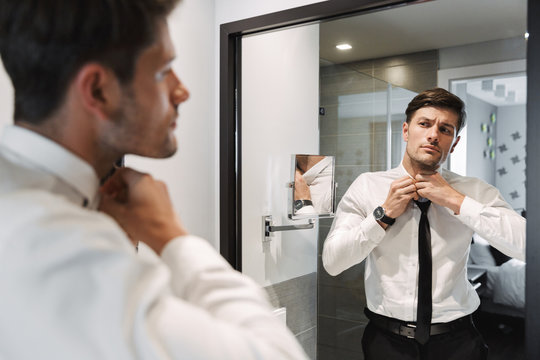 Image closeup of handsome man wearing formal suit looking at mirror in bathroom at hotel room during business trip