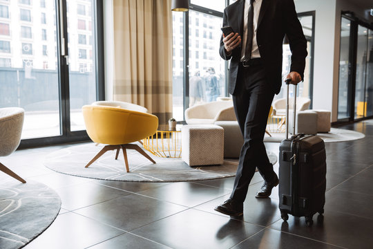 Cropped photo of successful businessman wearing suit holding smartphone and walking with suitcase in hotel lobby