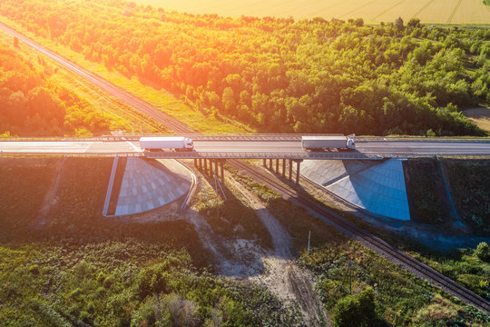 Aerial view of truck with cargo driving on highway route bridge in sunset light, industrial transportation and logistics