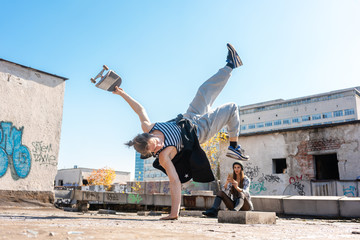 Man doing tricks and one-armed handstand on roof of abandoned building