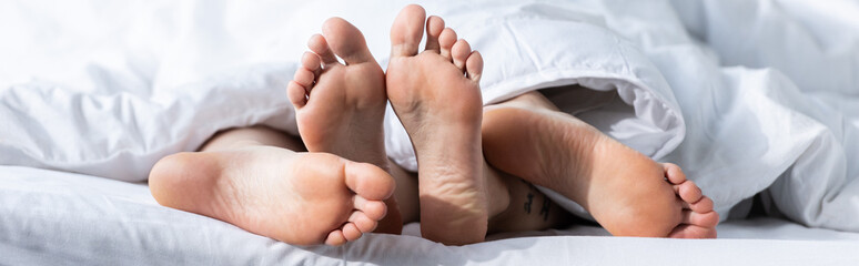 panoramic shot of two barefoot lesbians lying under blanket
