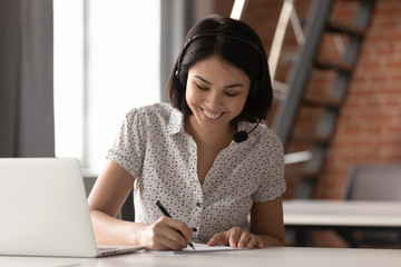 Happy asian businesswoman wearing headset make notes on conference call Fototapete
