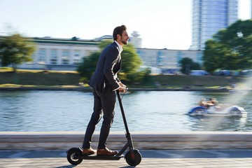 Young business man in a suit riding an electric scooter on a business meeting. Wall mural