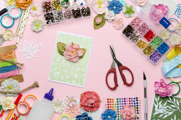 Paper flowers, scissors, homemade card, paper and scrapbooking items on pink background. Scrapbooking, top view