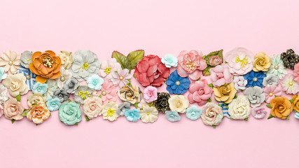 Lots of colorful homemade paper flowers on pink background in the center. Top view