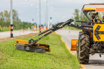 Tractor with a mechanical mower mowing grass on the side of the asphalt road.