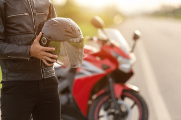 Handsome motorcyclist wear leather jacket and holding helmet on the road Wall mural