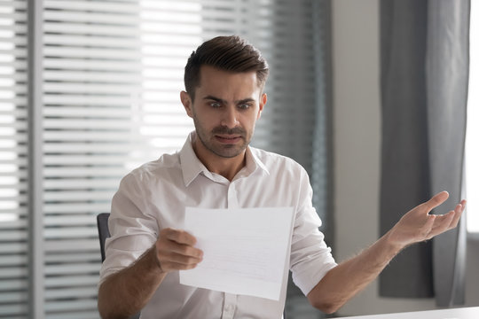 Shocked frustrated business man read bad news in paper letter