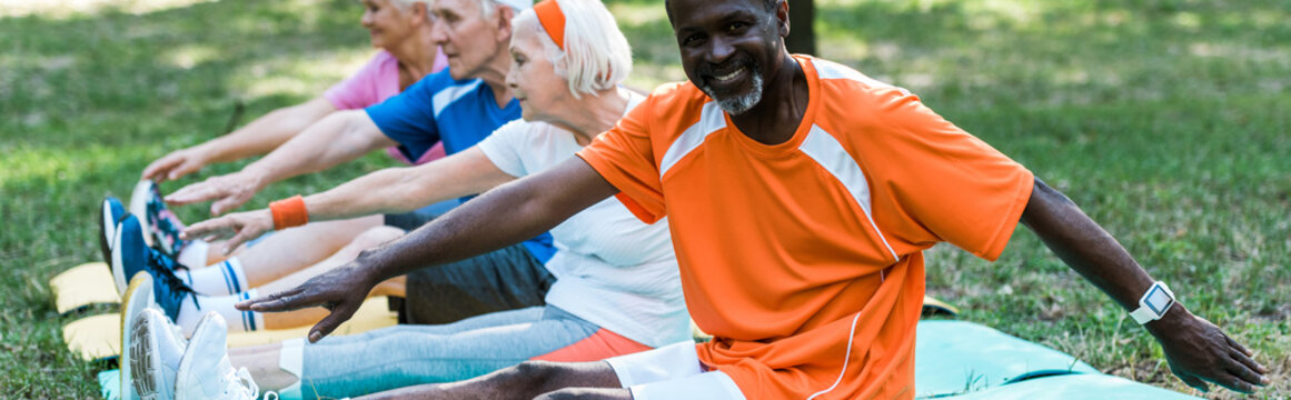 panoramic shot of happy african american man near retired pensioners in sportswear