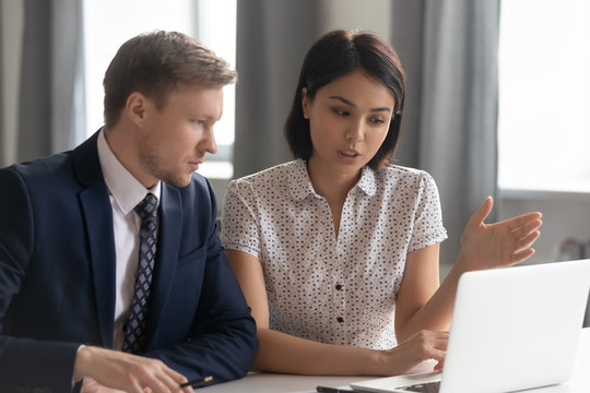 Asian manager mentor consult caucasian client teaching intern with laptop