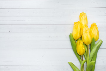 Fotobehang Tulp Bouquet of bright yellow tulips on a light table with copy space.