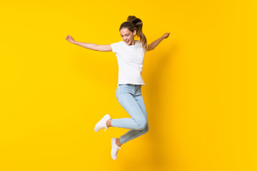 Young woman jumping over isolated yellow wall Wall mural