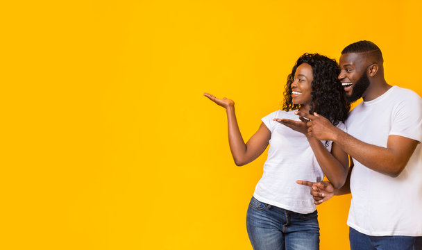 African-american man and woman point at empty space