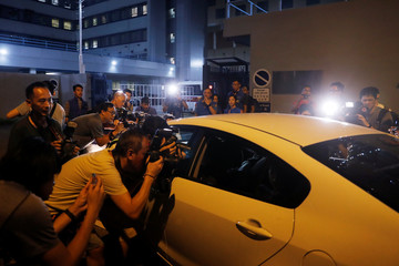 Photographers take pictures of a man in a car suspected to be involved in Sunday's Yuen Long after he was detained by police officers, in Hong Kong