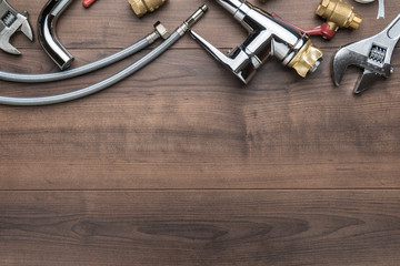 Top view of plumbing tools on brown table. Flat lay image of wrench, flexible hose connectors, mixer tap over wooden background with copy space. Upside composition of tools for plumber.