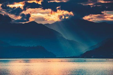 Wall Mural - The amazing fairy tale sunset over the freshwater Phewa Lake. The breathtaking colorful cloudy sky. The main tourist attraction of Pokhara city in Nepal.