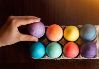 High angle of hand placing dyed egg with other colored Easter eggs.