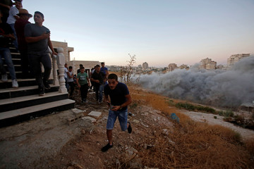 People run as Israeli forces blow up a Palestinian building in the village of Sur Baher which sits on either side of the Israeli barrier in East Jerusalem and the Israeli-occupied West Bank