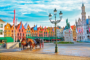 Photo sur Toile Bruges Horse carriages on Grote Markt square in medieval city Brugge at morning, Belgium.