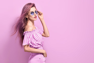 Fotobehang Kapsalon Fashion portrait Enchanting woman with trendy hairstyle, make up in stylish purple Outfit. Beautiful sensual long-haired slim model Girl in Trendy fashionable Sunglasses posing on purple.