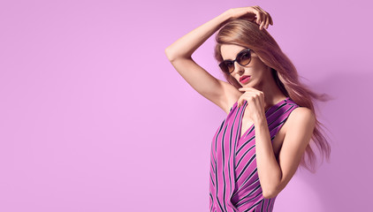 Wall Mural - Fashion portrait Graceful woman with trendy hairstyle, make up in stylish purple Outfit. Beautiful glamour long-haired slim model Girl in Trendy fashionable Sunglasses posing on purple.