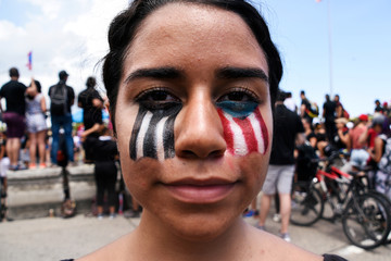 Demonstrator poses for a picture with her face painted during the national strike calling for the resignation of Governor Ricardo Rossello in San Juan