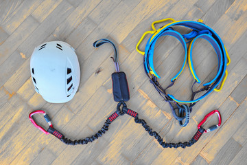 Flat lay of via ferrata gear (white helmet, two lanyards with shock absorber system, climbing harness) on wooden background with light orange spots.