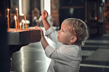 Little blonde boy in the church on Easter. Puts a candle to prays to God