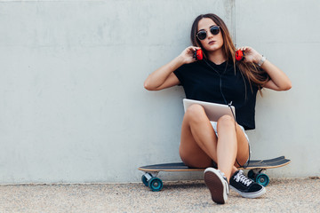 Photo sur Aluminium Magasin de musique Young woman sitting on skateboard and holding tablet