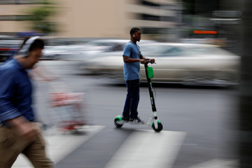 A man speeds along a downtown street atop a Lime scooter in Los Angeles