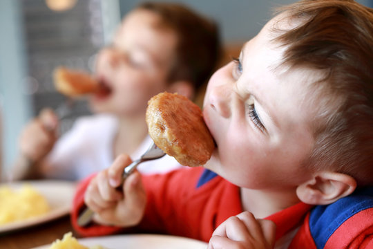 Two brothers eating cutlets