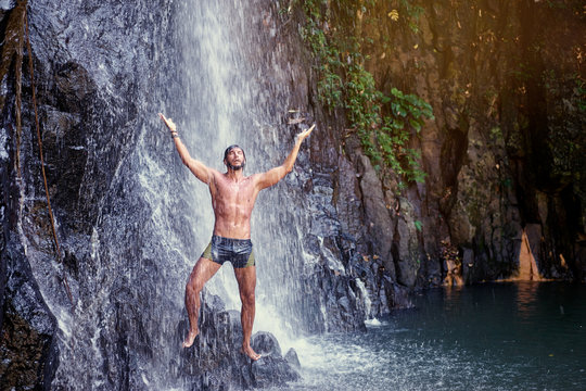 Happy young man relaxing under tropical waterfall with arms up raised in freedom. Health and relaxation.