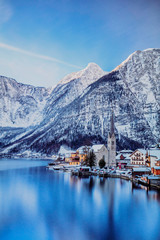 Typical village called Hallstatt con the Hallstatter see at sunrise with the houses reflecting in the lake